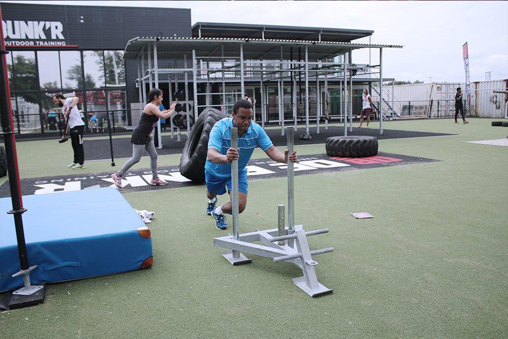 een oefening met de powersled op de stormbaan en een tyre flip oefening