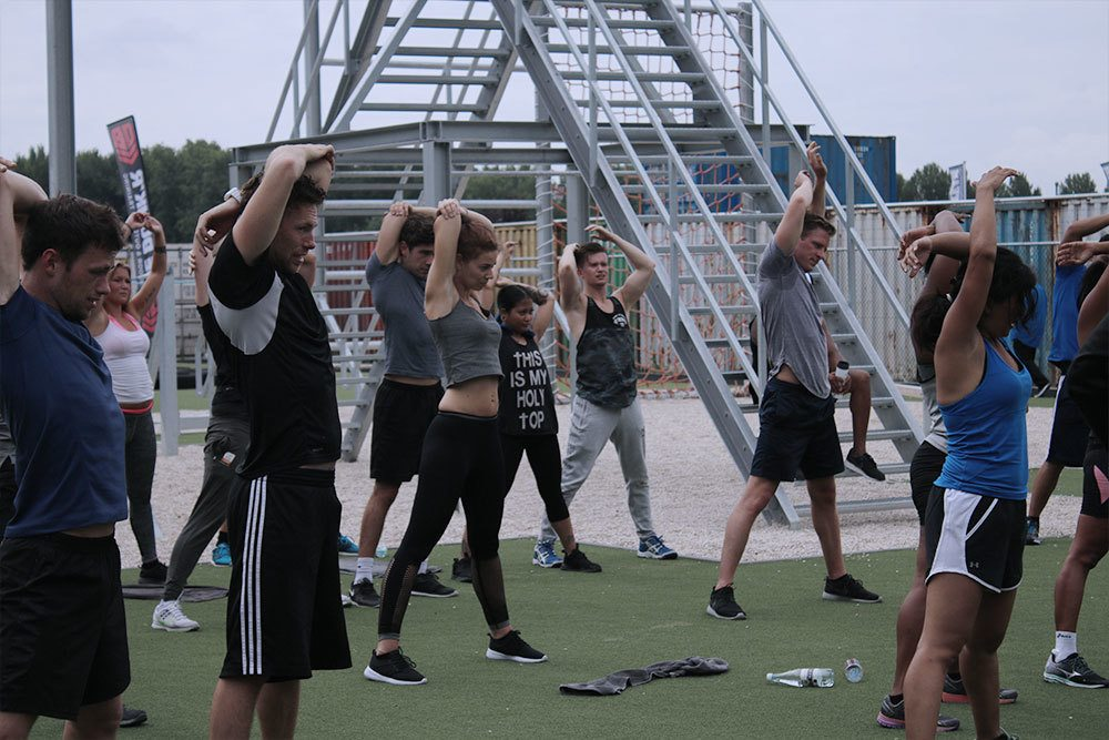 de deelnemers doen rek- en strekoefeningen op het outdoorterrein